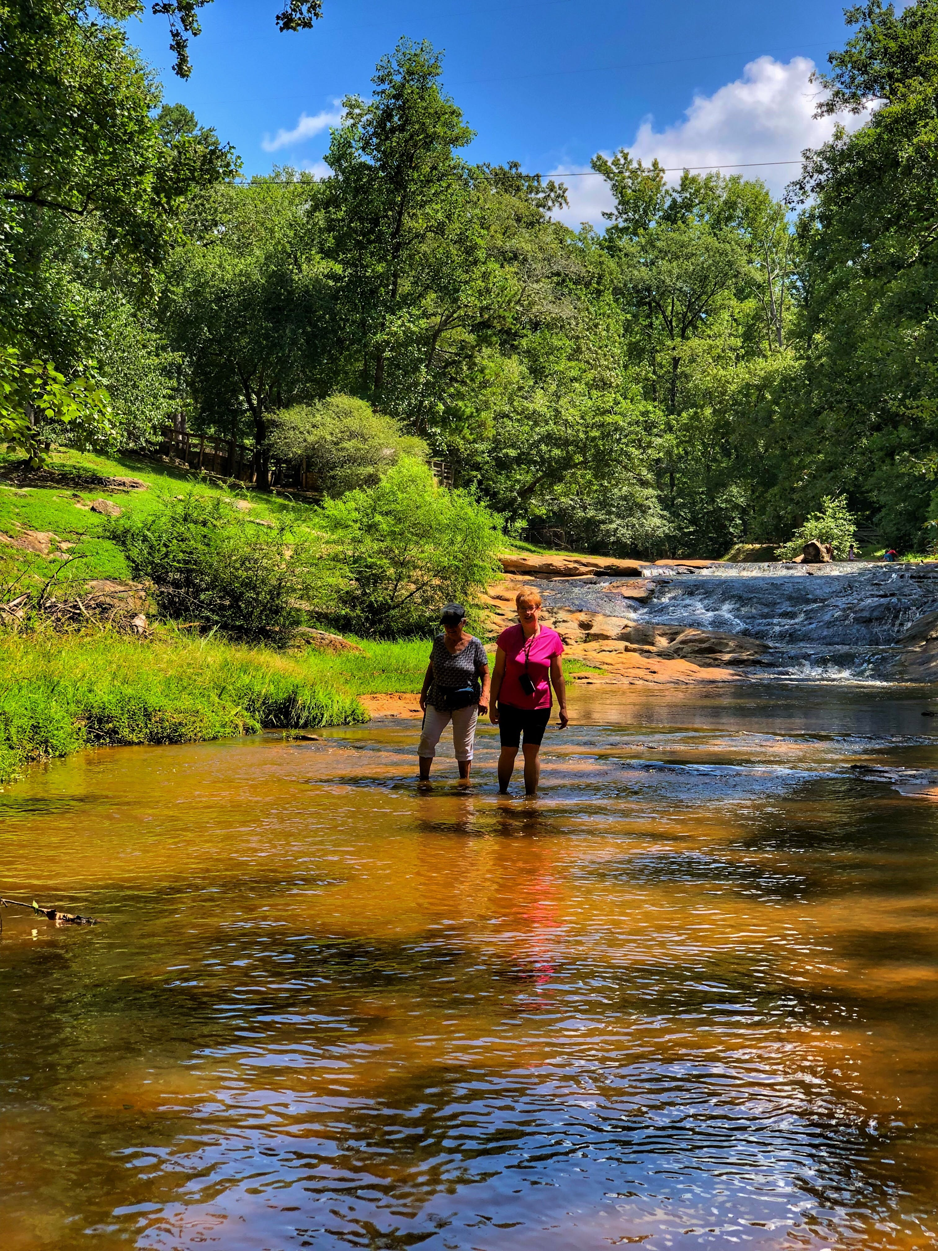 two campers wade in a shallow river in victoria bryant state park