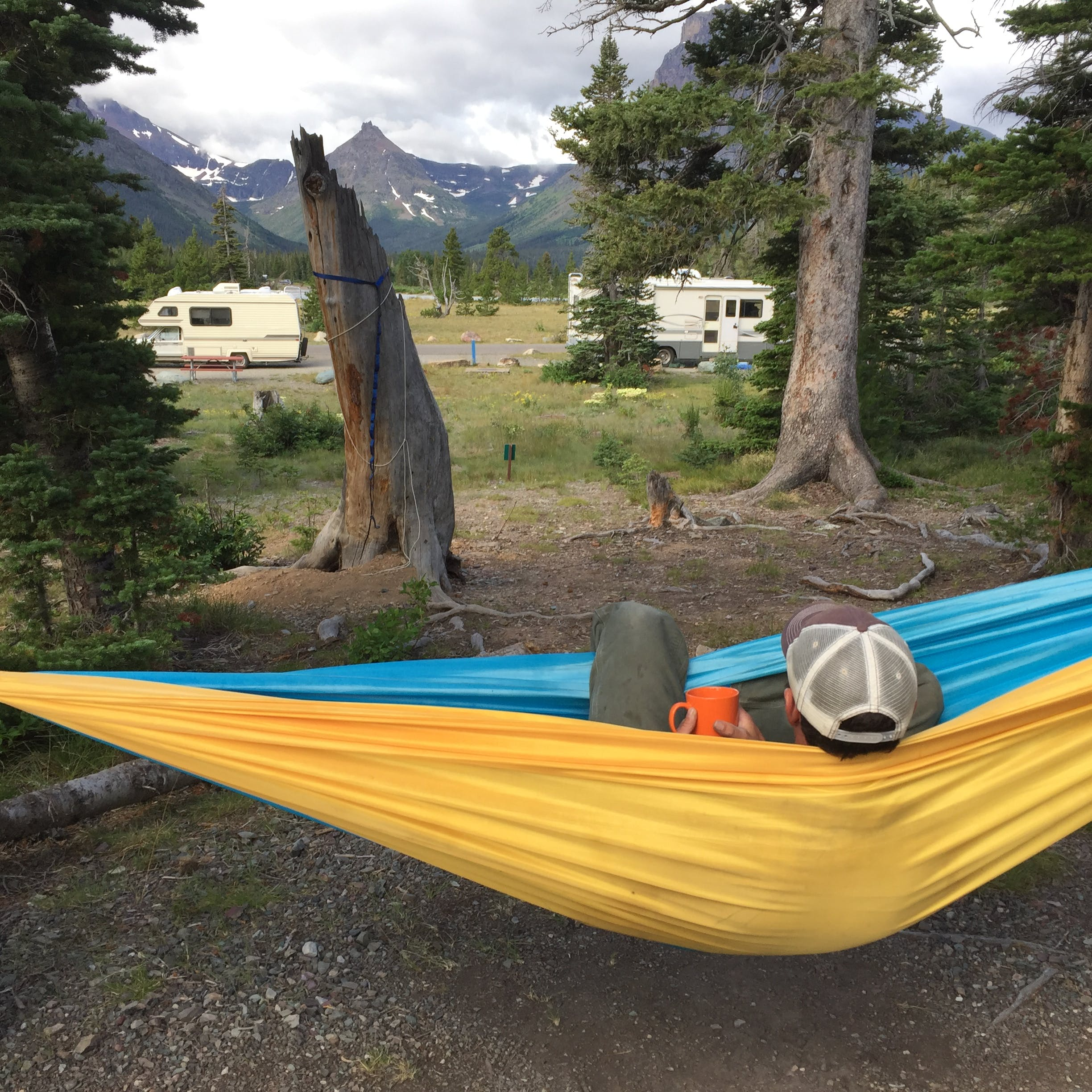 Person sitting in a yellow hammock at an RV site