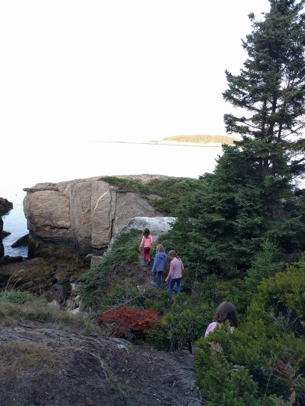 Four young girls walk together on a hike on Hermit Island, Maine.