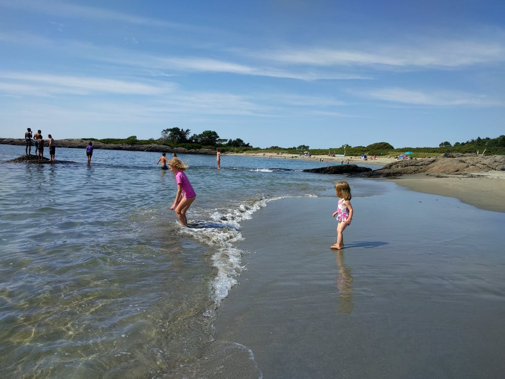 Young girls play in the shallow beach on the shore of Hermit Island, Maine