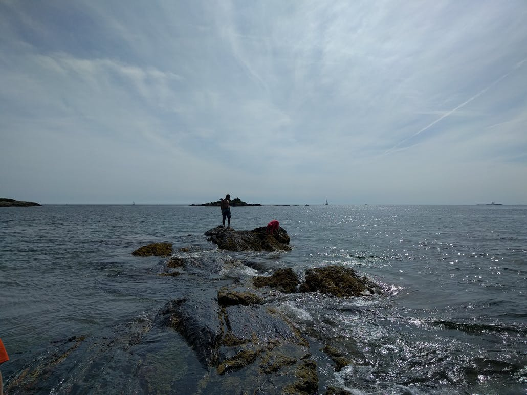 A man looks down from a rocky outcropping in the Atlantic Ocean, off the coast of Hermit Island, Maine