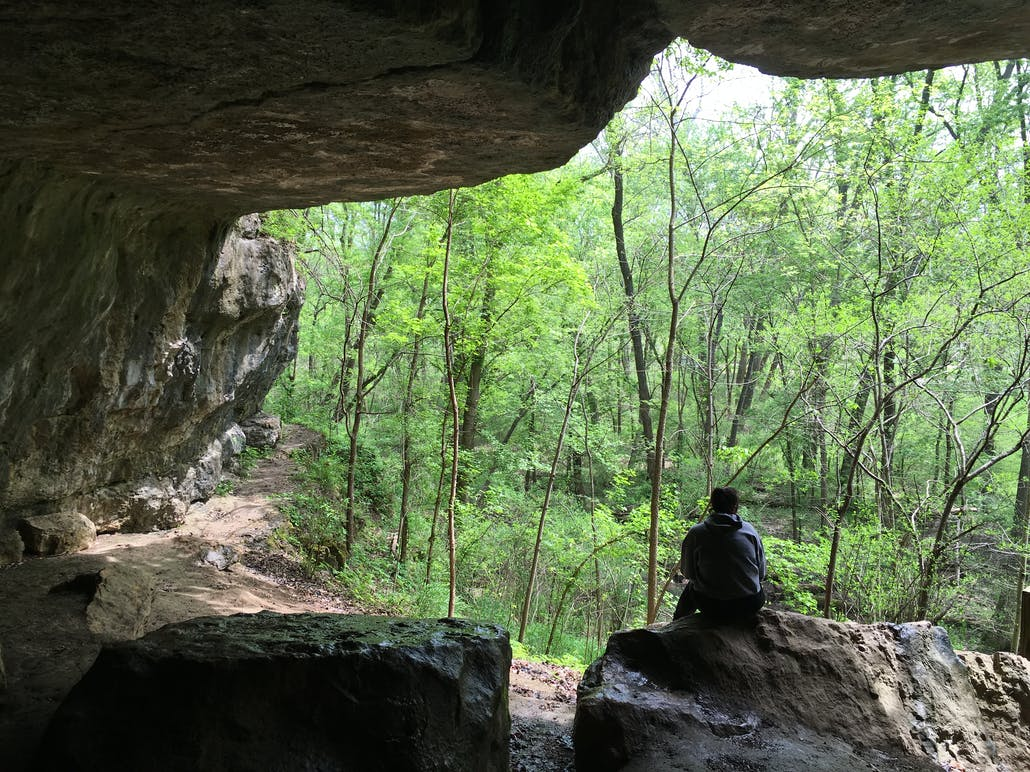hiker sitting on a boulder in meremac state park cave