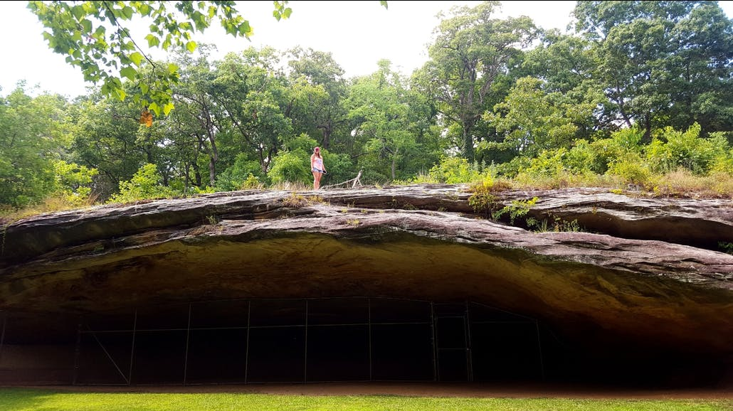 female hiker stands atop graham cave