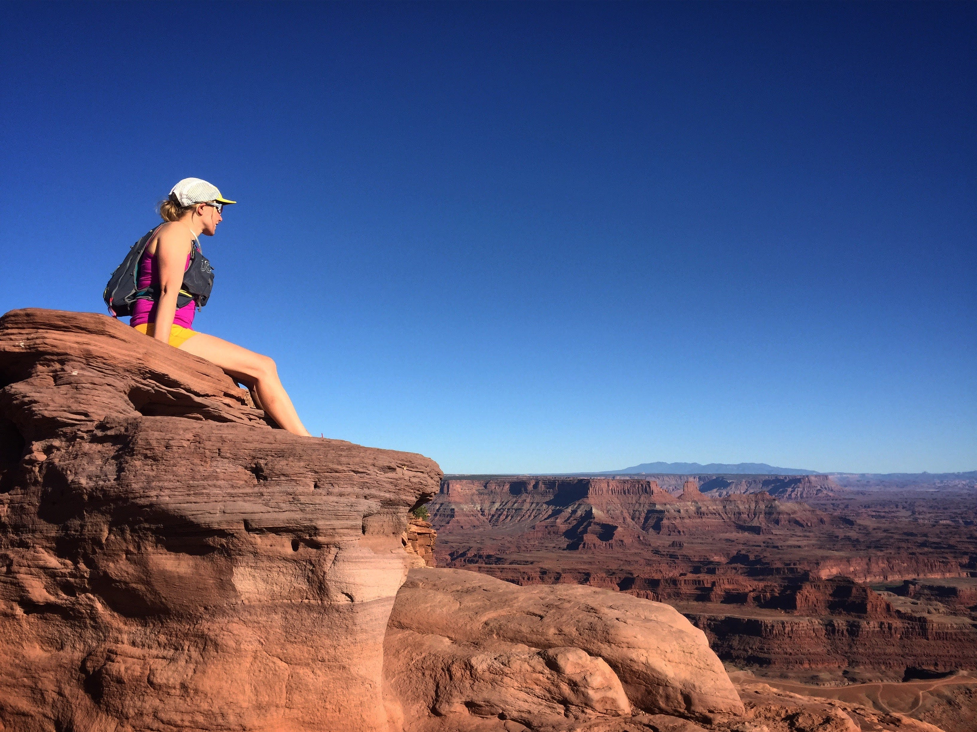 woman looking over cliff dead horse point state park, utah