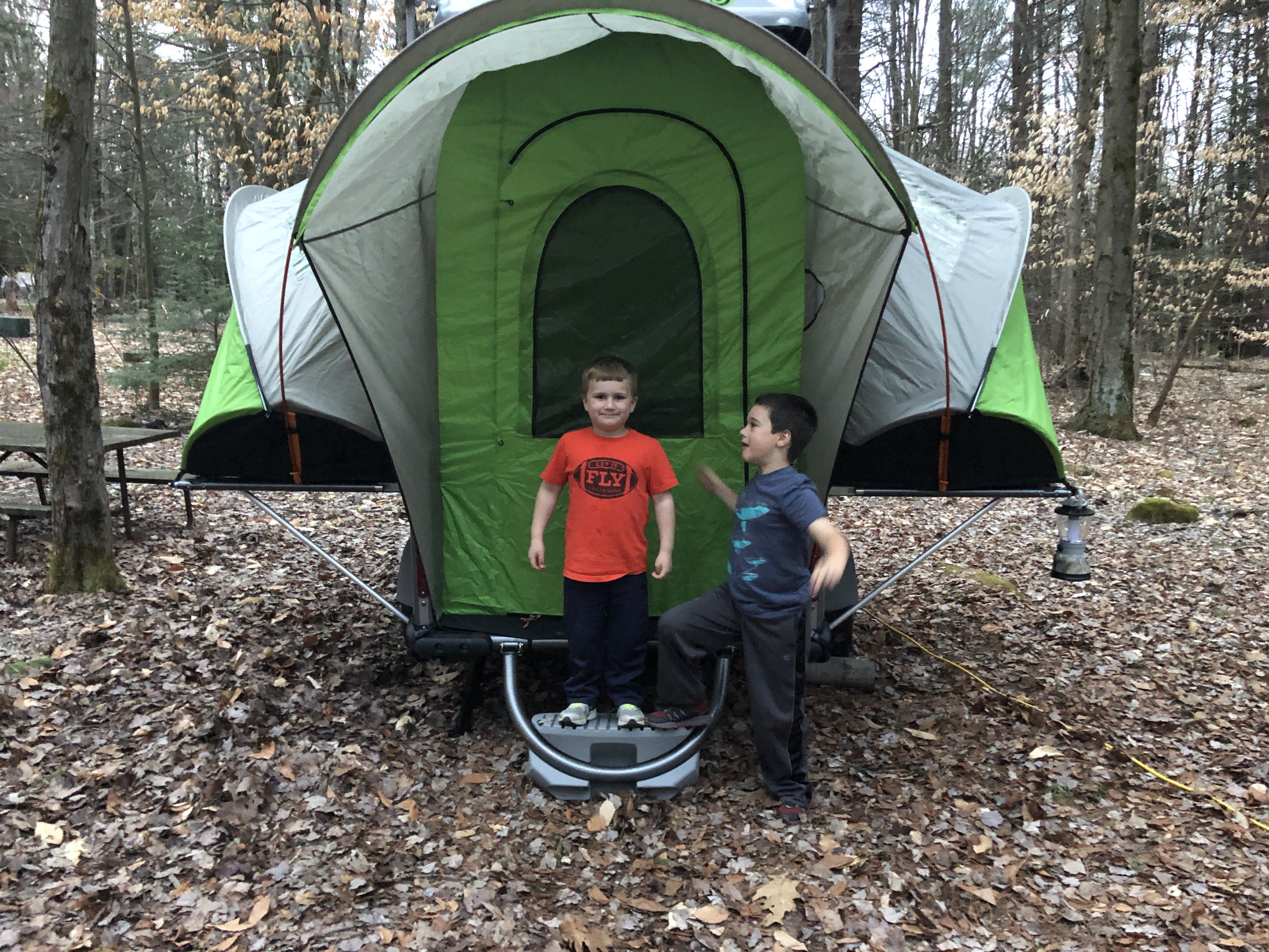 2 Boys stand in front of green unconventional tent structure in the woods.