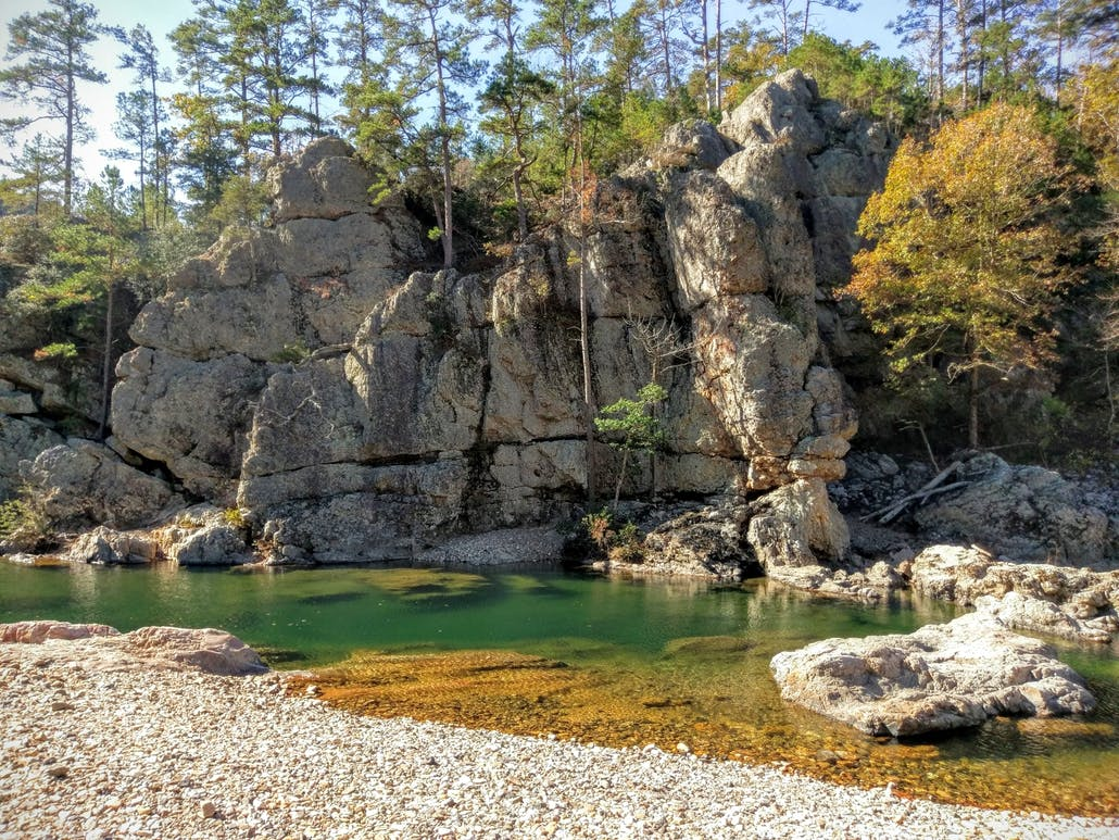 A rock wall looks down upon a clear water river in the Ouachita National Forest