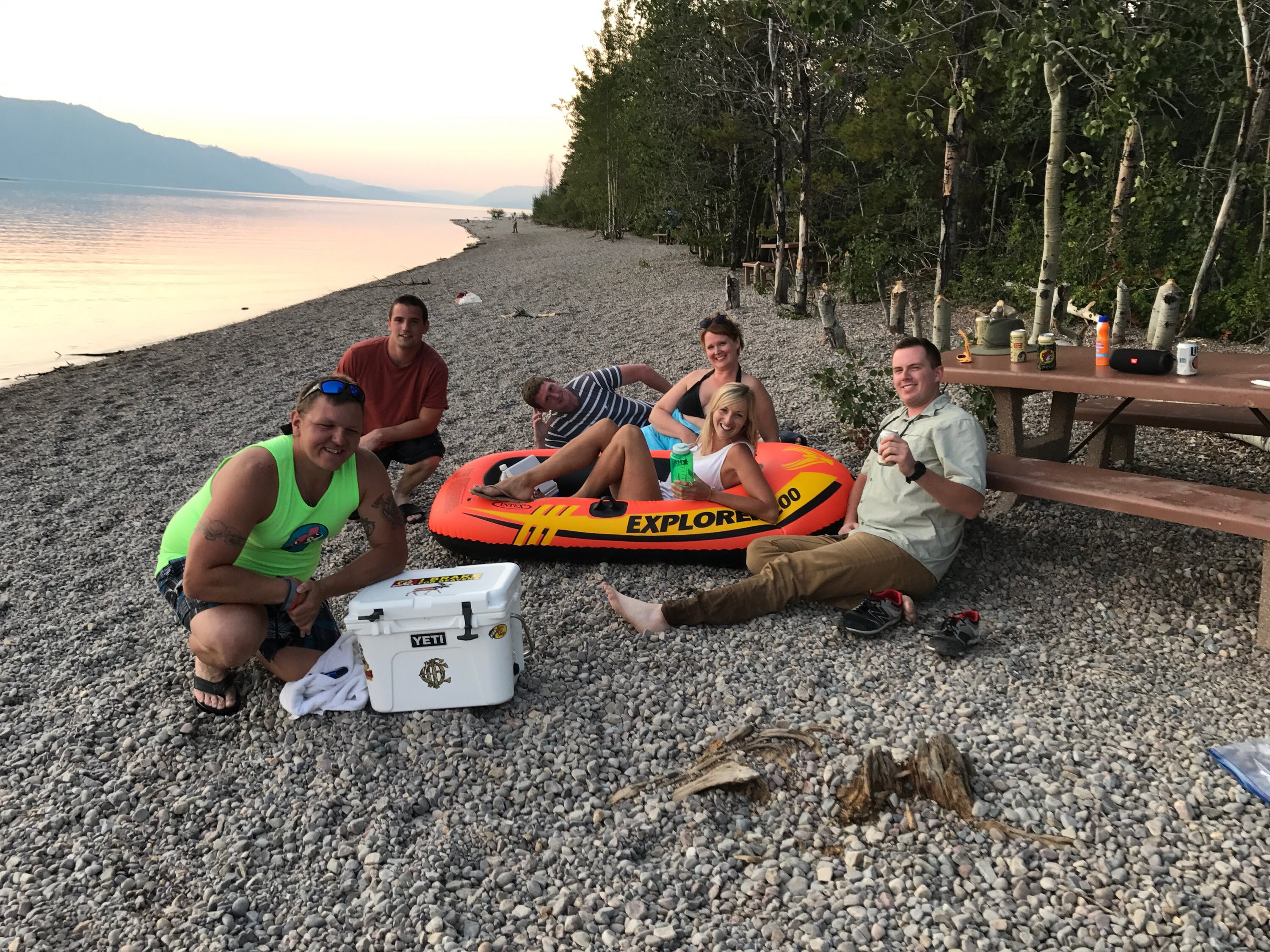 group of campers relax on the banks of jenny lake in wyoming