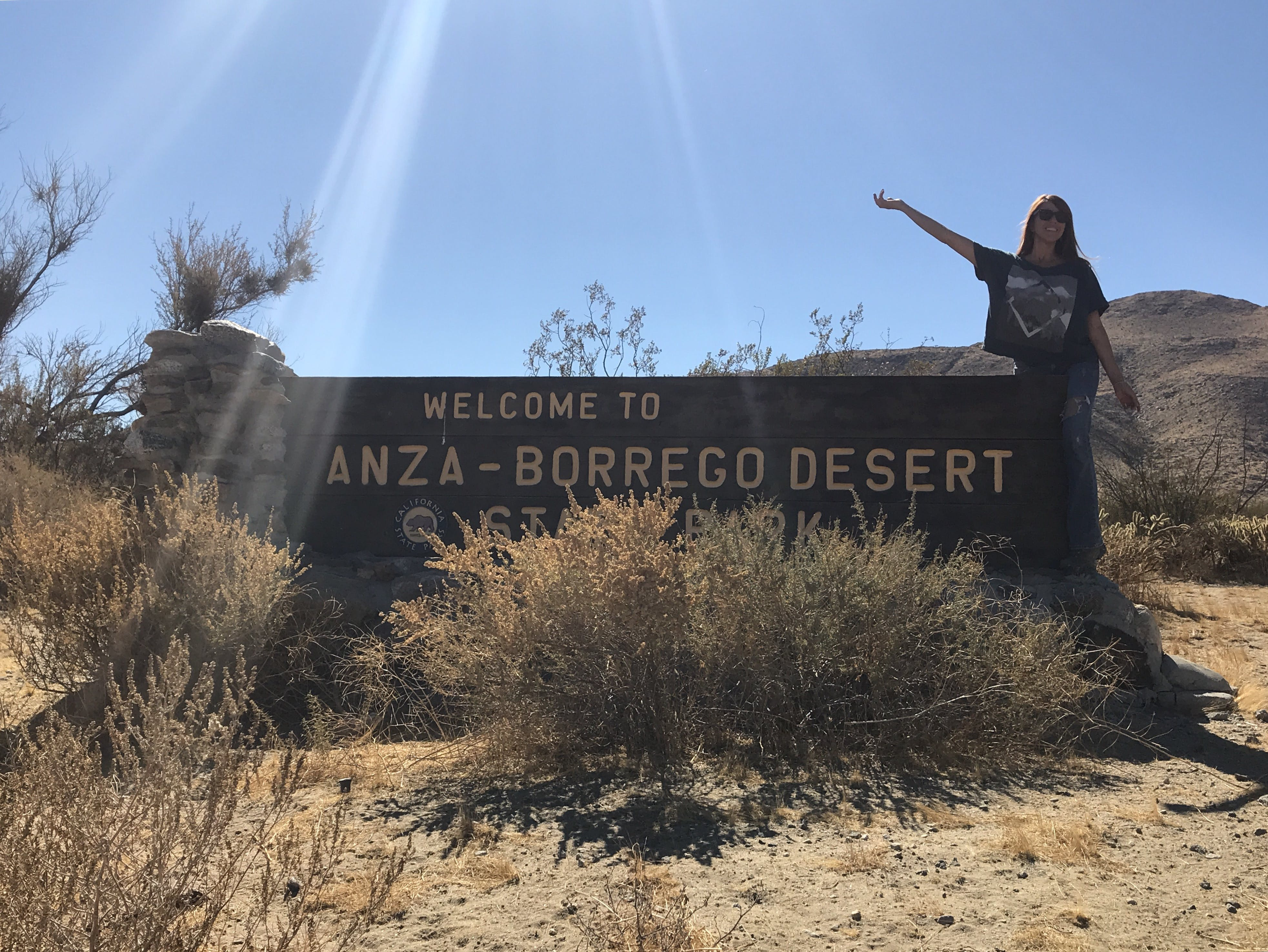 visitor poses beside the welcome sign to the woman poses for photo running away from a dinosaur sculpture in the anza-borrego desert